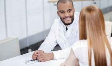 Smiling doctor talking to patient