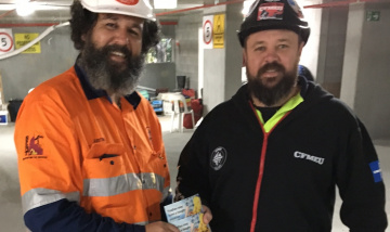 Mates in Construction distribute awarness postcards onsite
