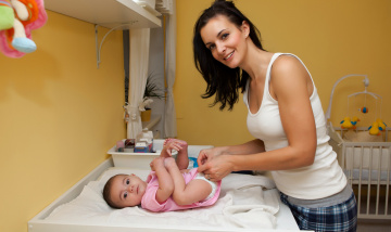 Mum caring for baby, changing nappy