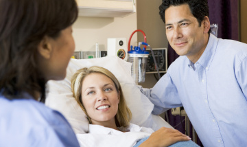 Pregnant woman and man talking to doctor in hospital